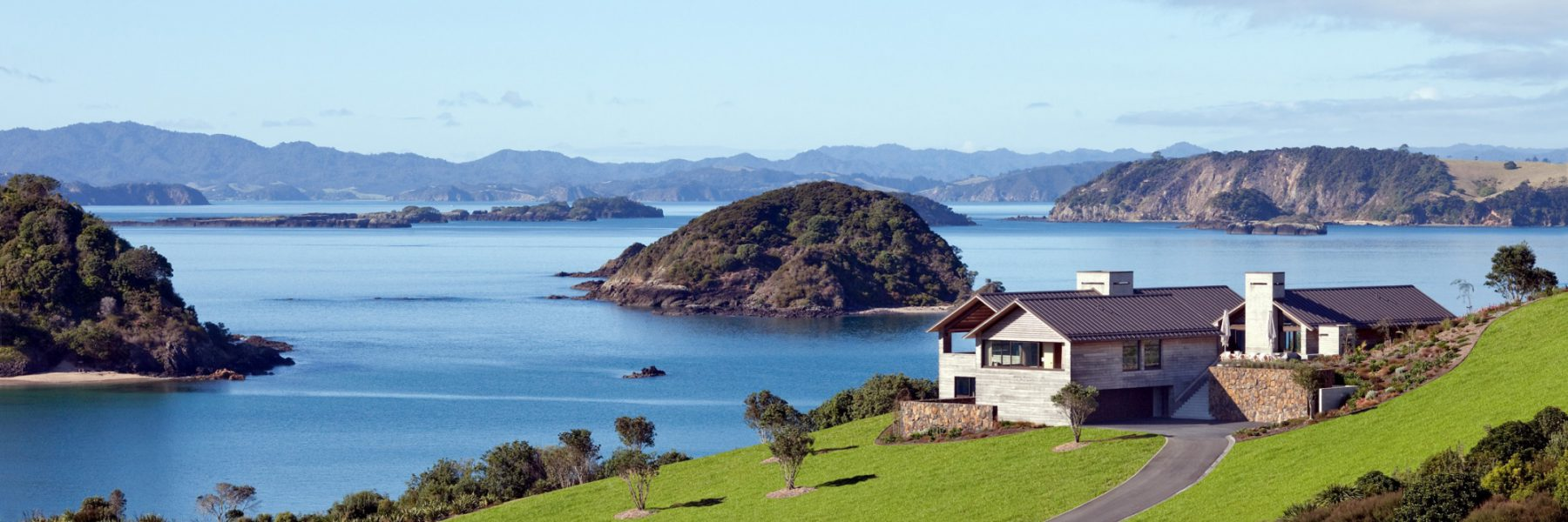 View of The Landing with rolling green grounds and the Bay of Islands in the background