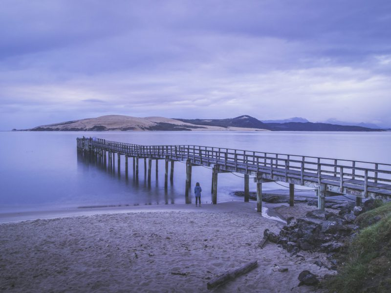 Looking across Hokianga Harbour towards sand dunes, with wharf in the foreground