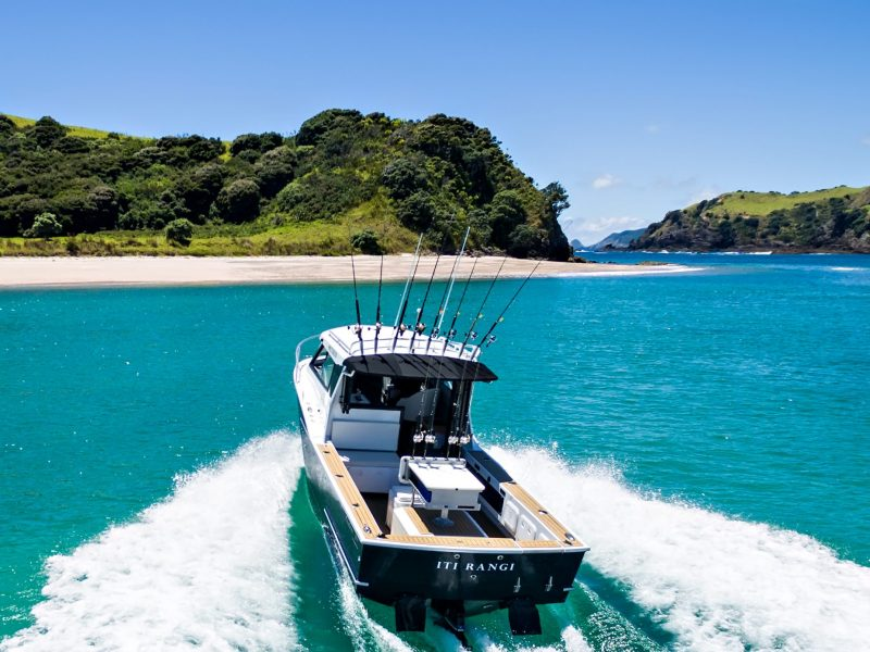 Fishing boat driving on turquoise water in the Bay of Islands