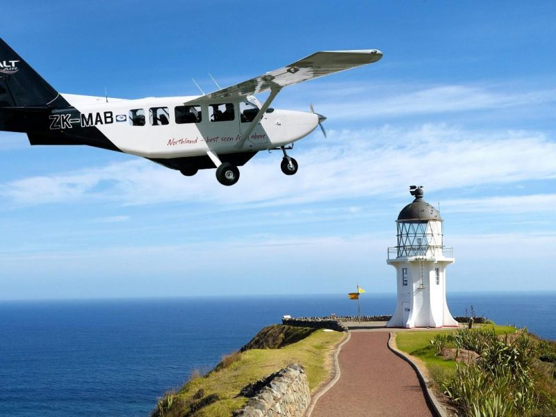 Small aeroplane flying over lighthouse at Cape Reinga, Northland