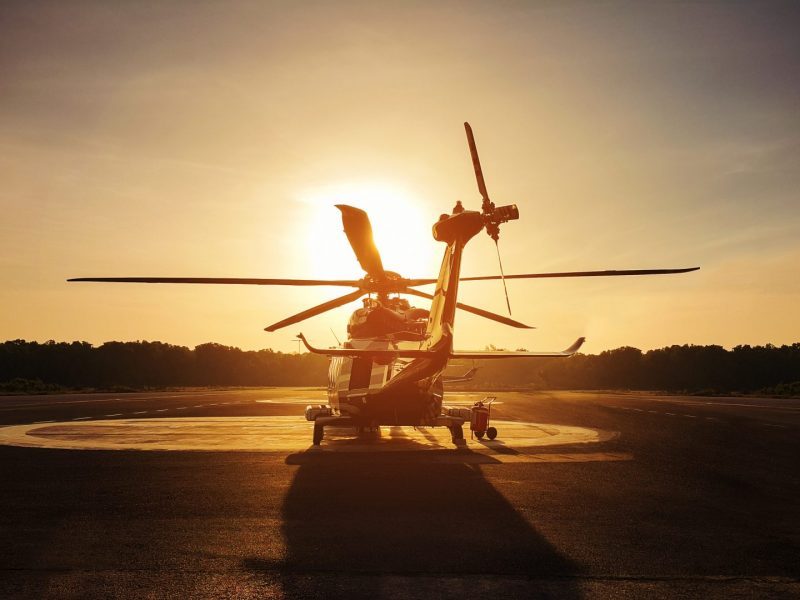 Helicopter parked on runway with sunset in background