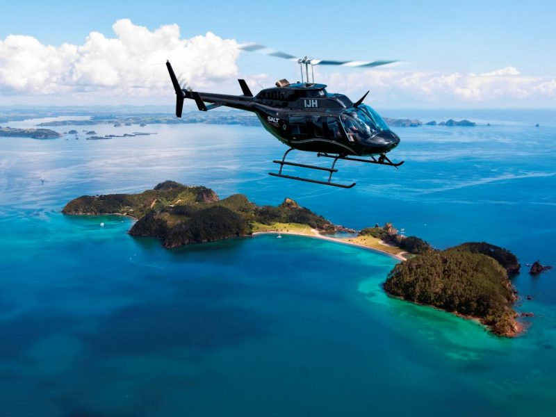 Helicopter flying over Roberton Island in the Bay of Islands with beautiful turquoise water